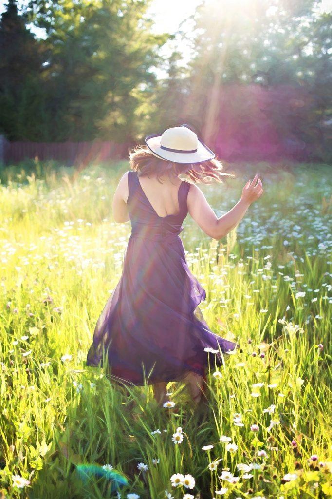 pretty woman in field, dancing, sunshine